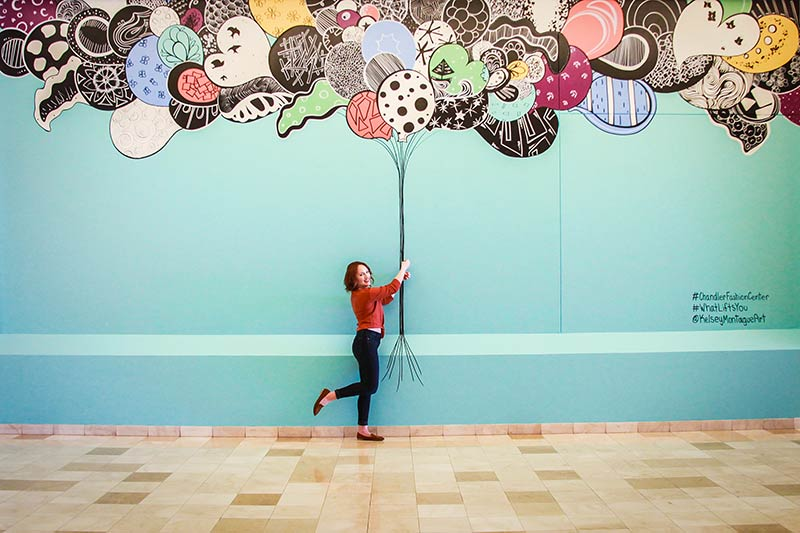 Kelsey Montague mural of holding balloons at Chandler Fashion Center