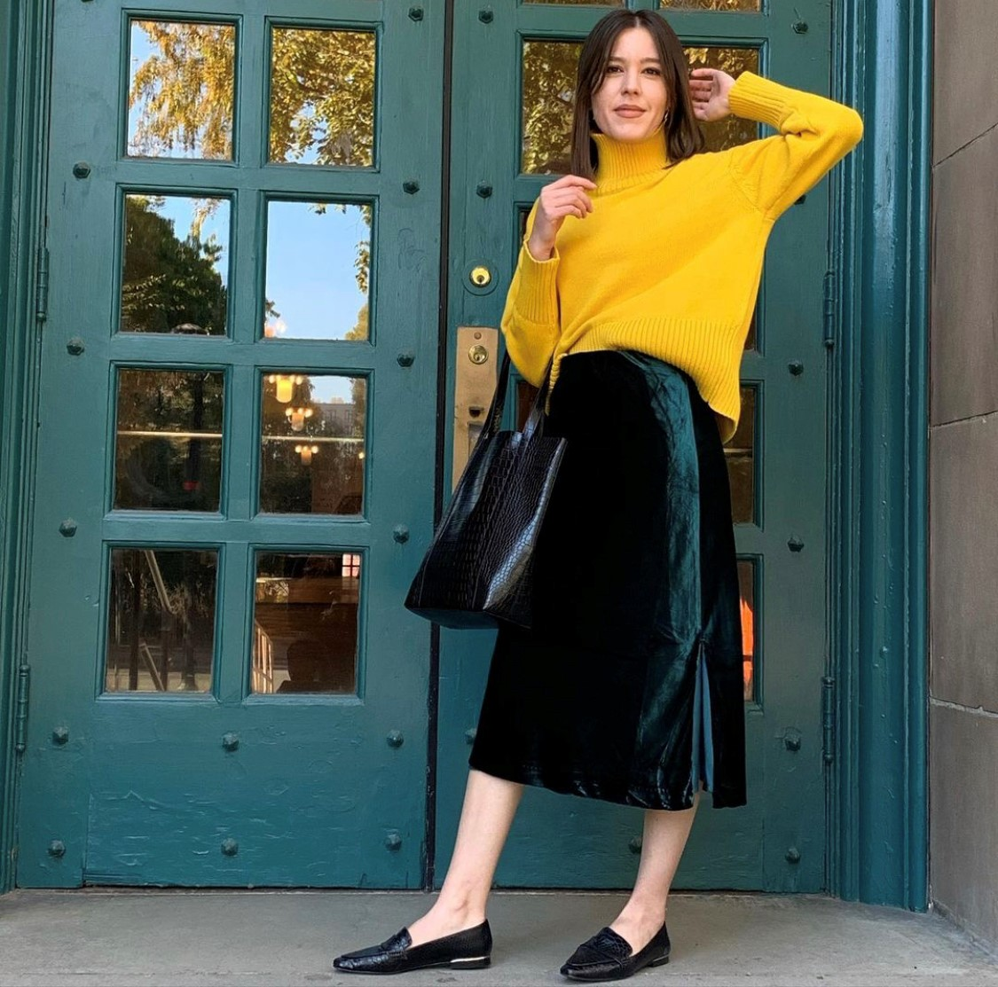 Ann Taylor Stylist with yellow turtleneck, forest green velvet skirt, black loafer shoes and tote bag.