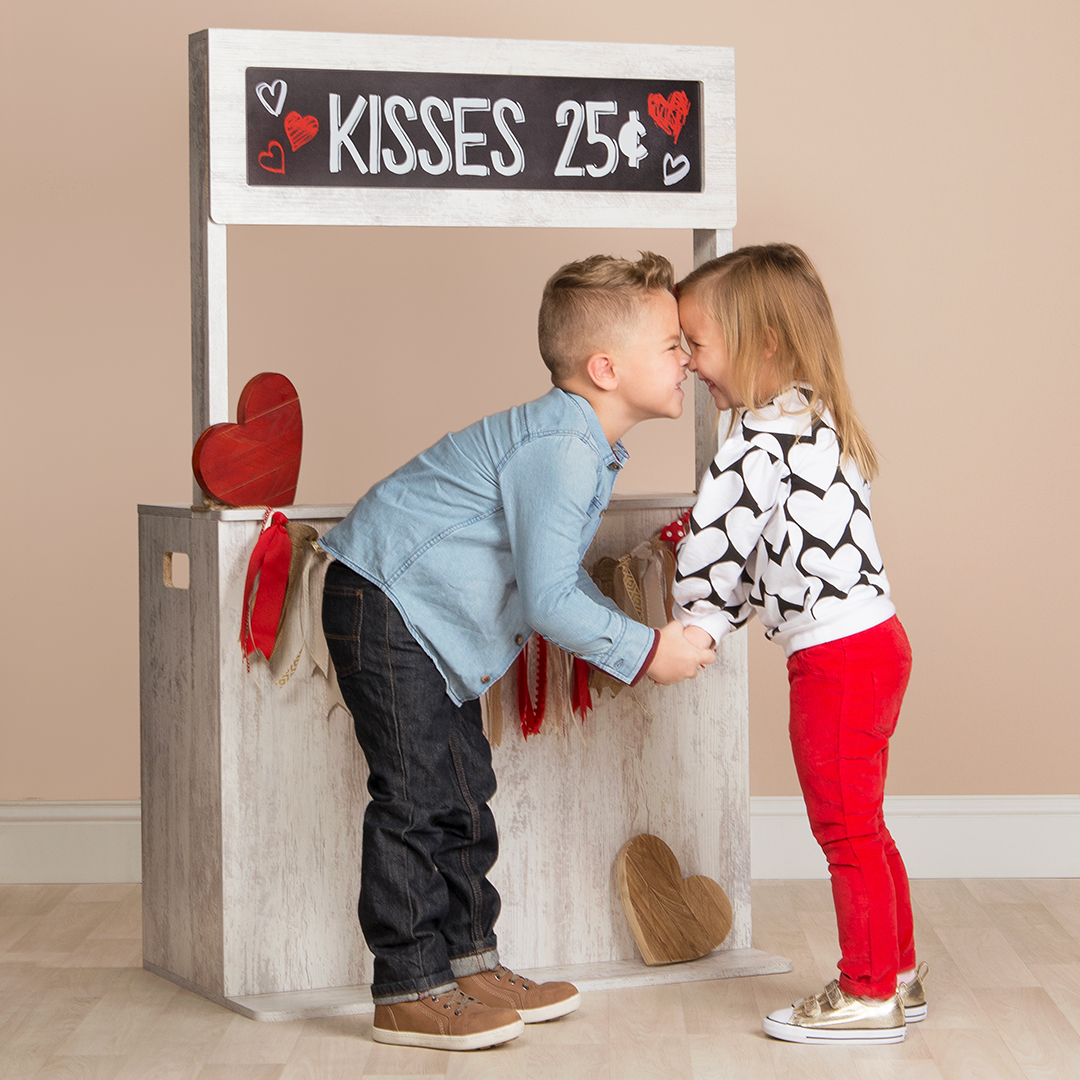 A girl and boy posing in front of a Valentine's Day photoshoot prop booth.