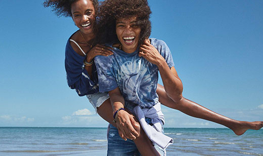 Two American Eagle Outfitters models smiling joyfully with an ocean background.
