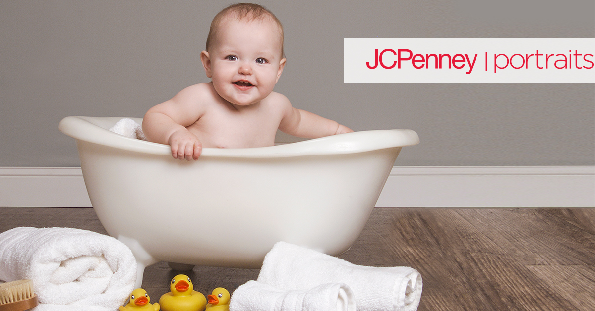 Baby sitting in white bath tub surrounded by ducks and bath towels