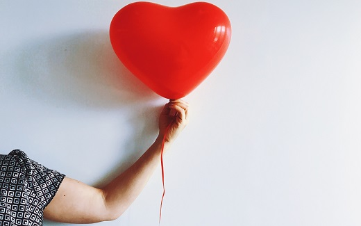 Woman's arm holding a red balloon with a white backdrop