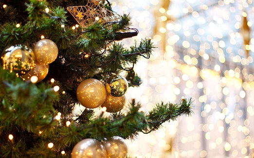 Green christmas tree with yellow lights and gold ornaments and a gold glitter background.