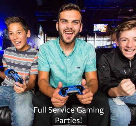 Boy with grey and pink striped shirt and blue jeans, guy with green shirt and boy with black shirt and blue jeans playing video games.