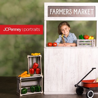 little girl with brown hair standing behind a Farmers Market stand with red tomatoes, green and yellow vegetables.
