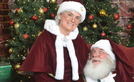 Santa and Mrs Claus wearing red and white hat with red and white cape with green christmas tree background.