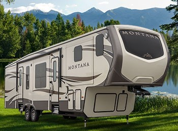Tan and brown recreational vehicle parked on green grass with green trees and blue mountain ridge background.