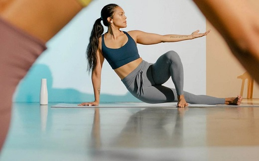 woman with black hair and blue yoga top in yoga pose.