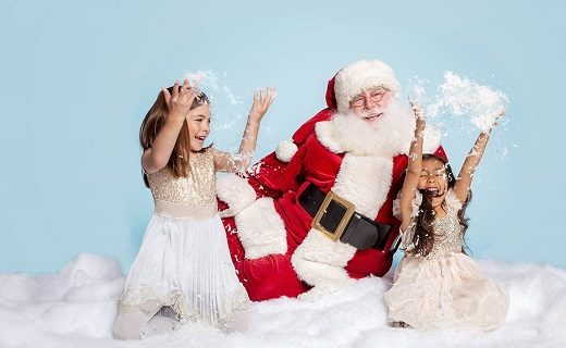 Santa in red suit with white beard and two girls with white dresses playing in snow.