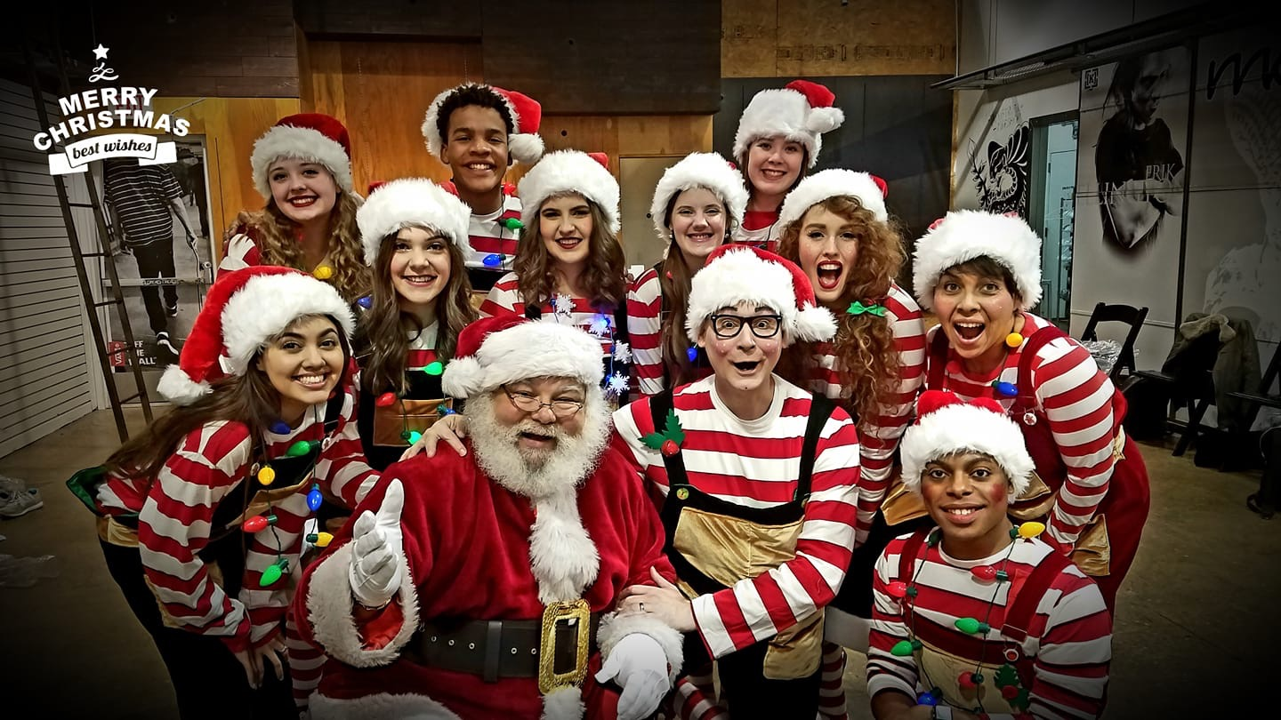 Santa with a group of carolers dressed as elves