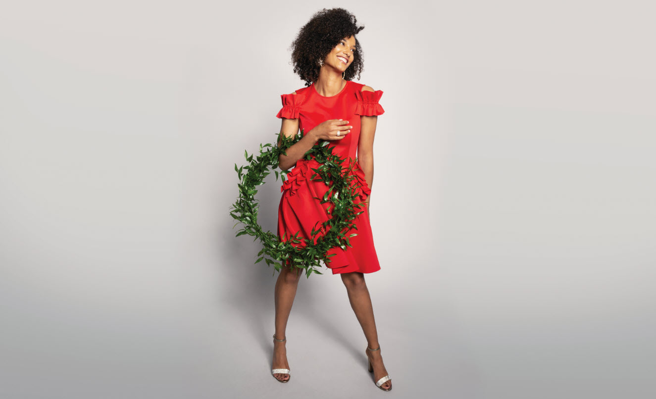 Curly-haired girl in red dress holding wreath