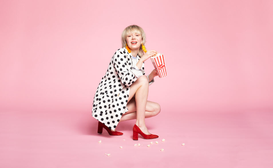 Woman in polka-dots kneeling eating popcorn on pink background