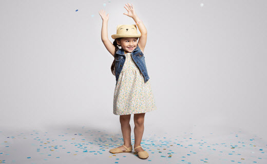Little girl in dress playing with blue confetti