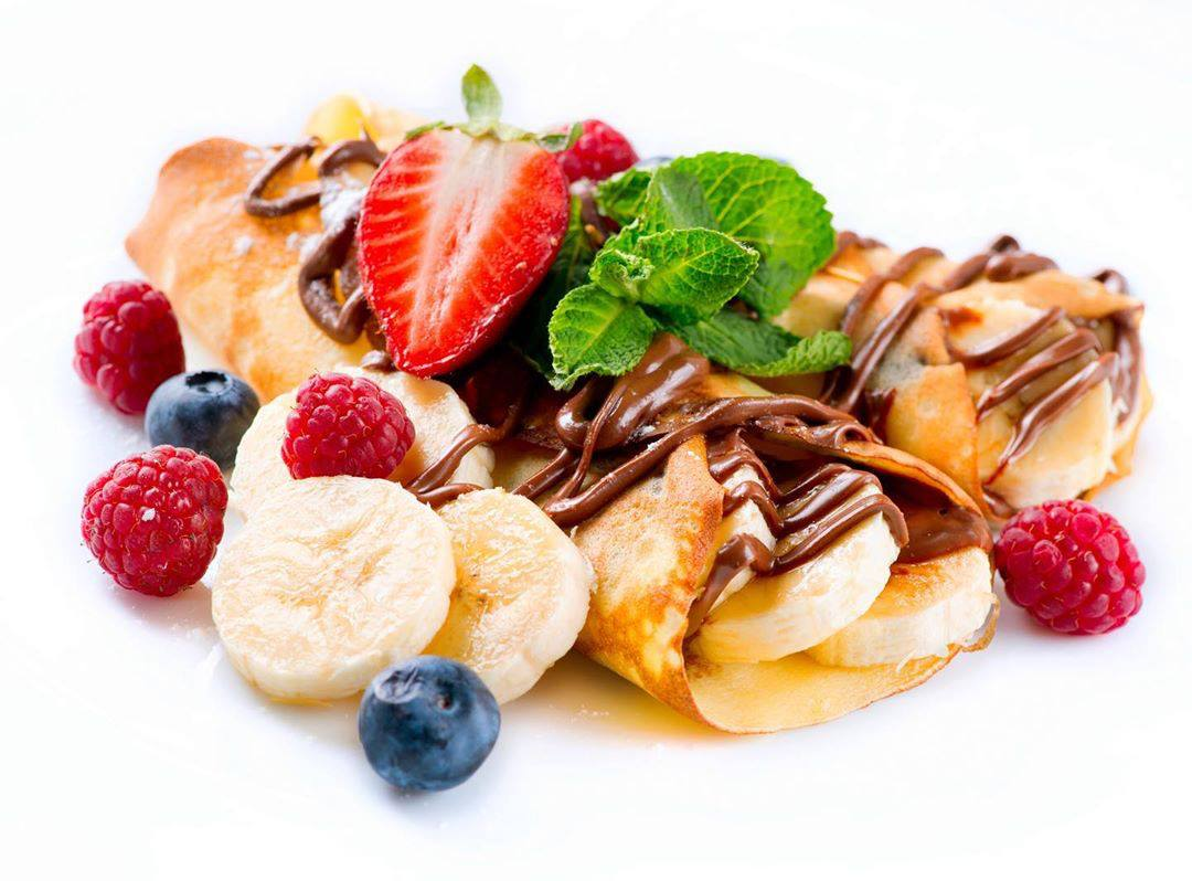 Closeup of crepes with berries, bananas and Nutella