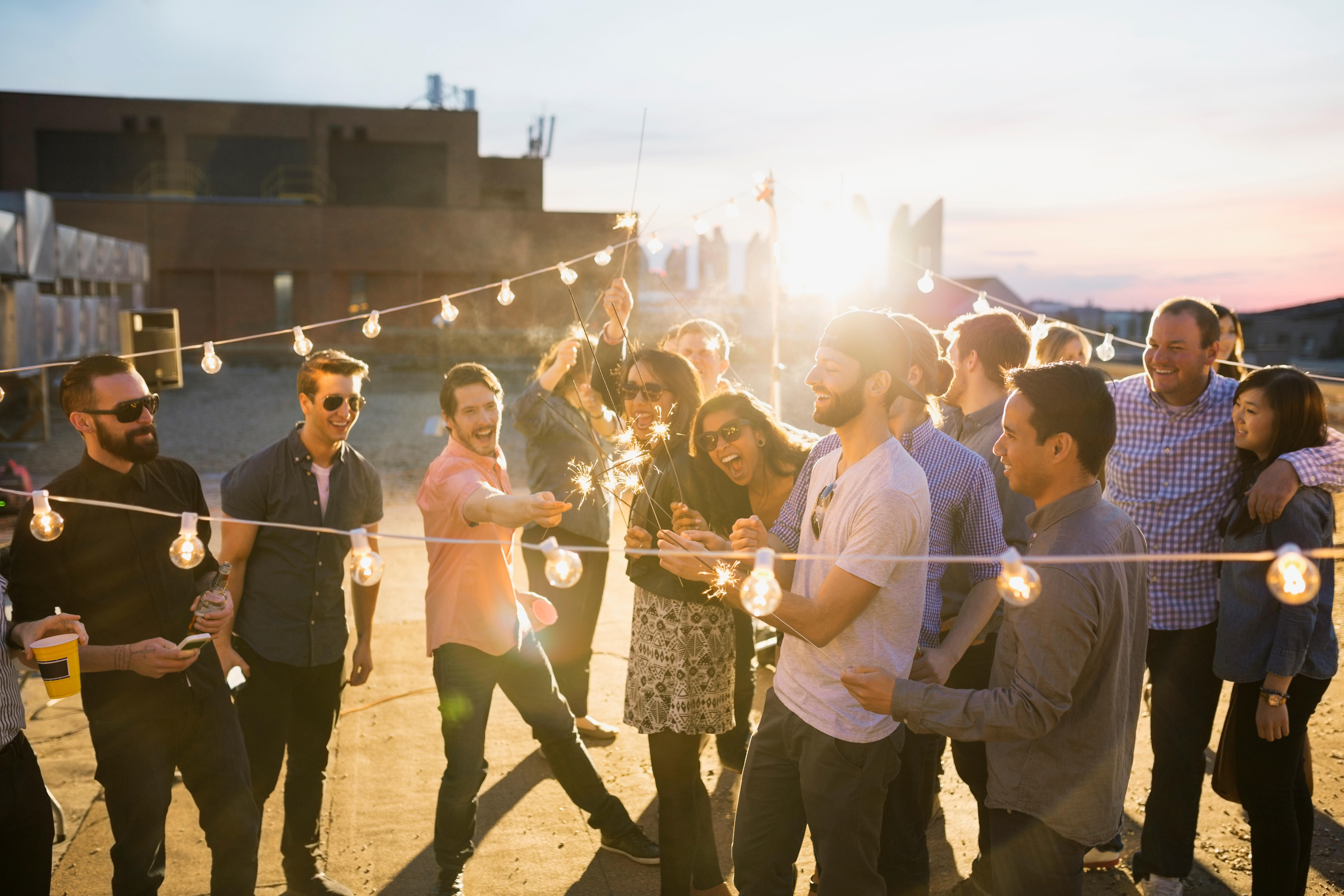 Young adults having a rooftop party at sunset