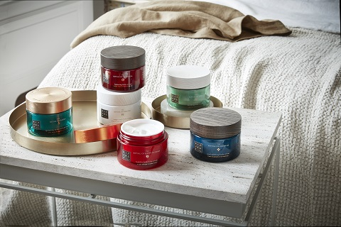 Six containers of Rituals body cream on table at the foot of a bed.