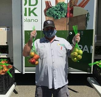 Volunteer at Food Bank holding bags of fruit.