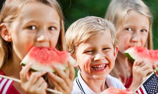 Three children - 2 girls and 1 boy - eating watermelon.