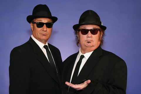 Photo of the Briefcase Blues Brothers in black suits, ties, sunglasses and hats.