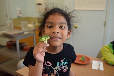 Little girl at a table holding broccoli.