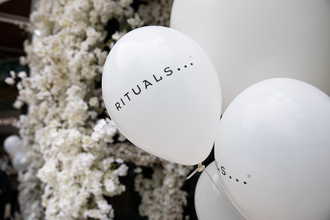 White balloons with the word Rituals on them, in front of flowers.