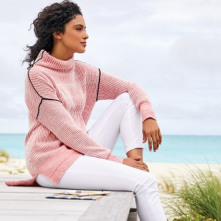 Woman wearing pink sweater and white pants sitting on beach.