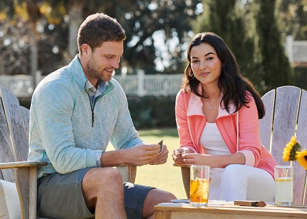 Man and women sitting at table with drinks.