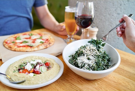 Two people eating True Food Kitchen entrees including humus, a salad and pizza.  They are also drinking a glass of wine and a beer.