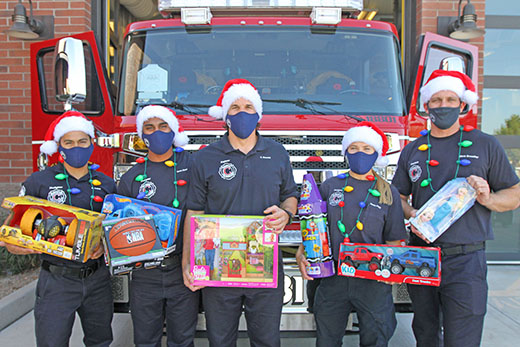 Chandler Fire fighters in masks holding toys in front of a fire truck.