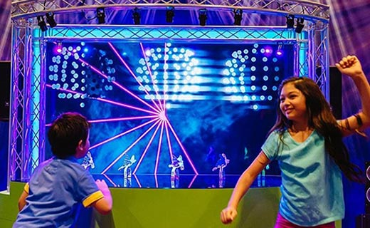 A boy and a girl dancing at a Crayola Experience exhibit of a mini stage with laser lights