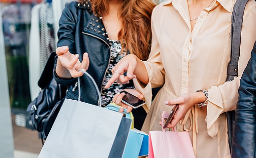 Two women standing outside and holding shopping bags open. One woman is pointing to what is inside the shopping bag.