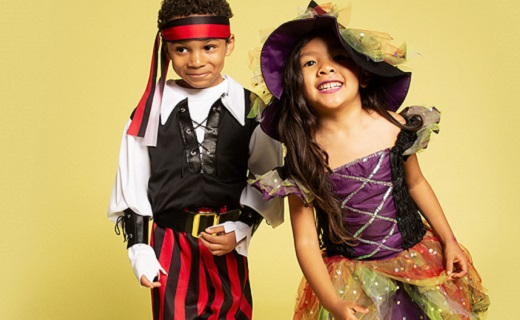 Boy in a pirate costume and girl in a witch costume for Halloween, standing next to each other laughing.