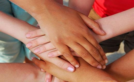 Kids layering their hands in community spirit.