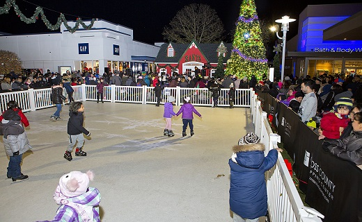 People skating on an outdoor ice rink with Santa's house and Christmas tree in the background.