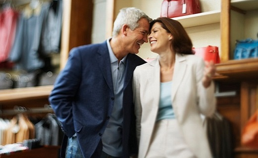 Man and Woman dressed in suits, standing inside a store and laughing together.