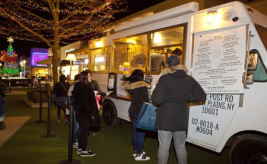 Customers in line at a food truck, outside, during Christmas season.