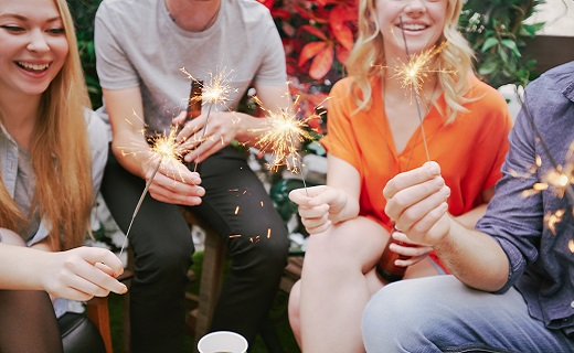 group of friends sitting outside holding sparklers in their hands and laughing.