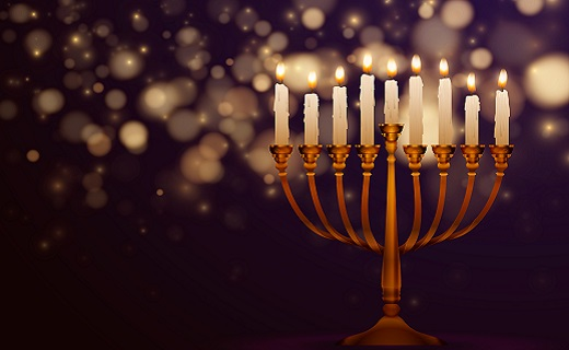 Menorah with lit candles and lights in the dark background.