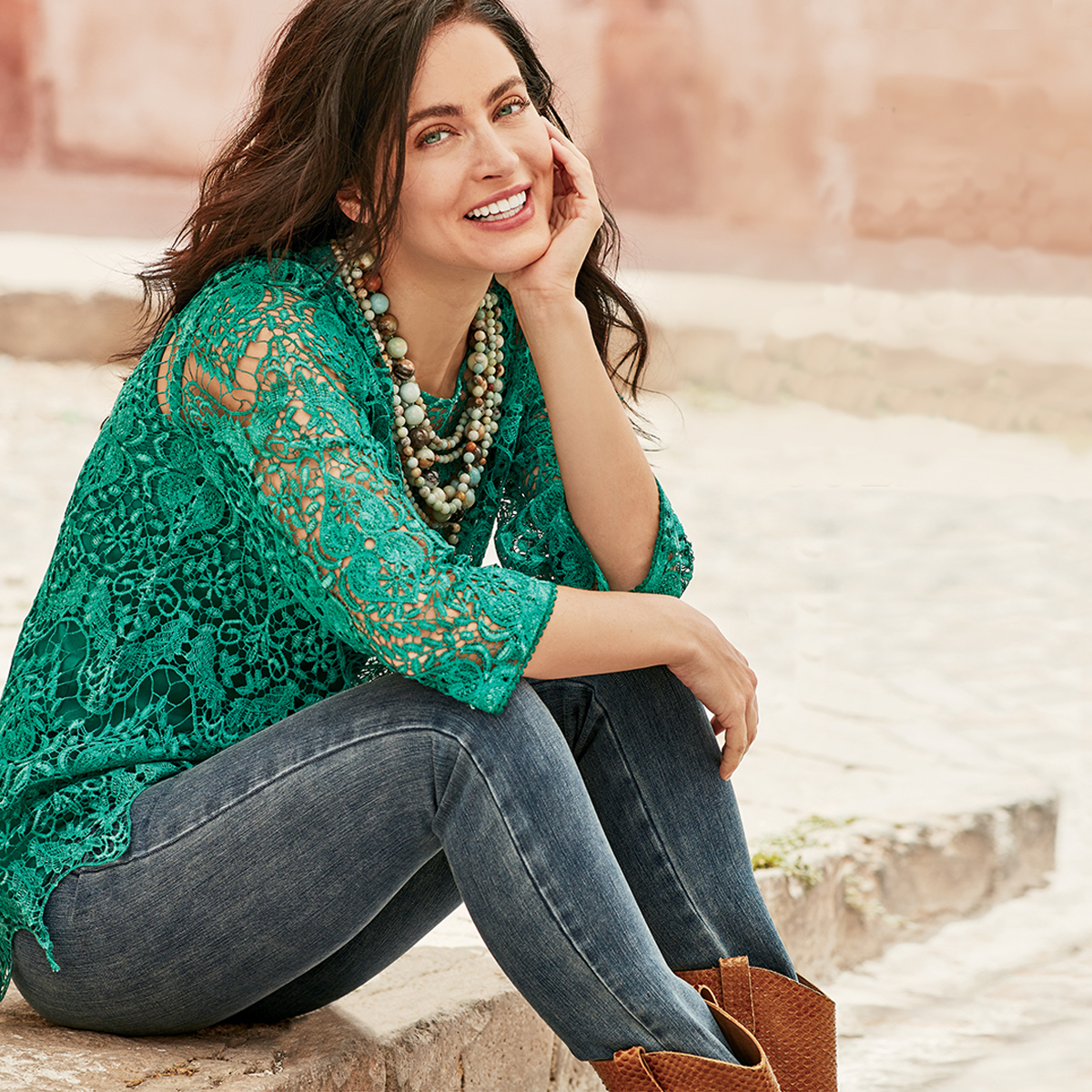 Woman in green shirt, jeans and tan boots, sitting.