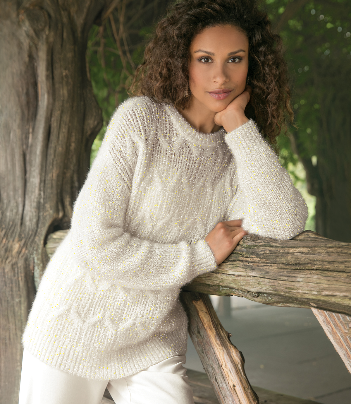 Woman wearing white sweater and white pants.