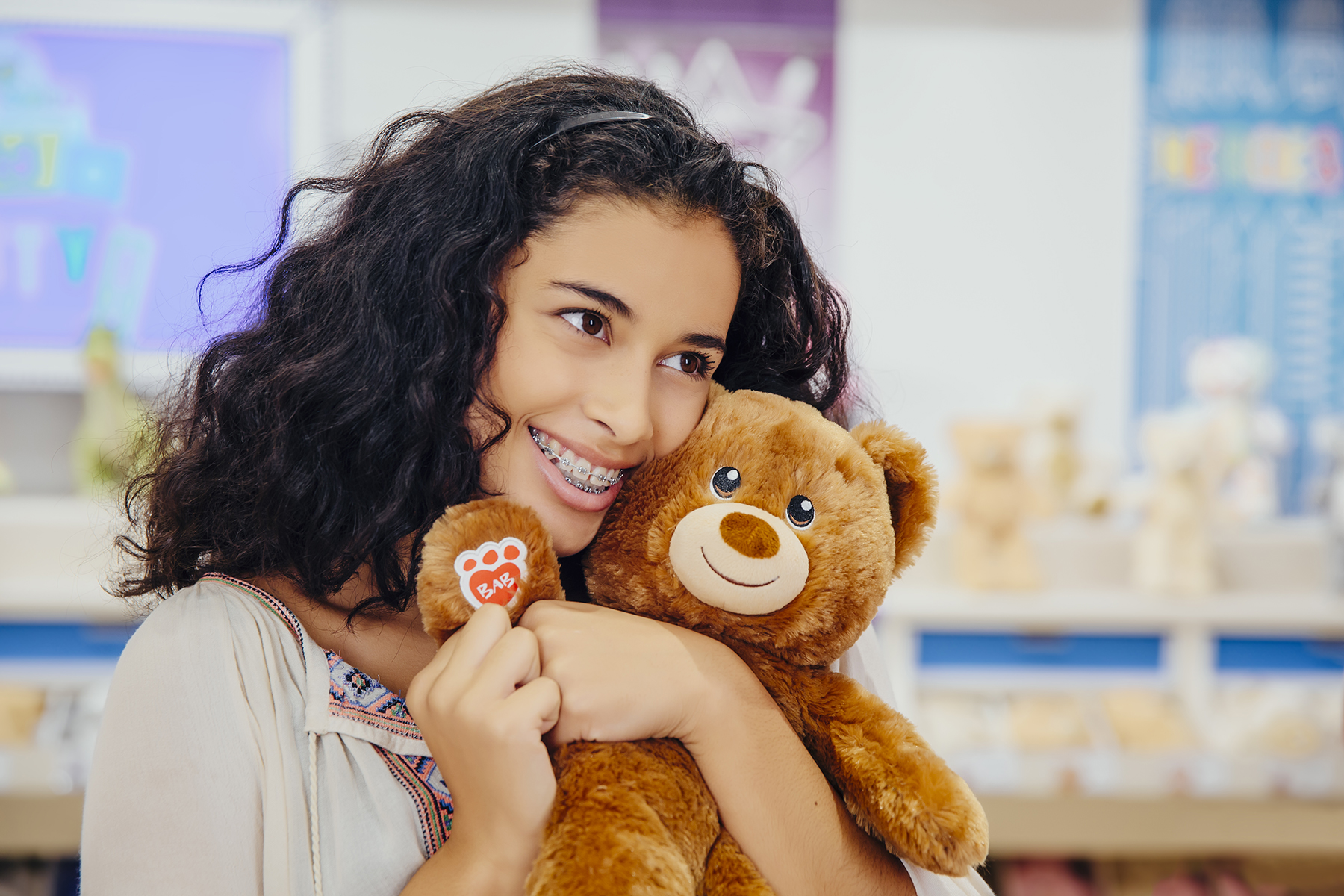 Young girl holding a brown teddy bear.