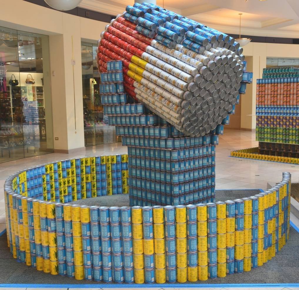 Structure of a hand holding a can good made out of cans of food.