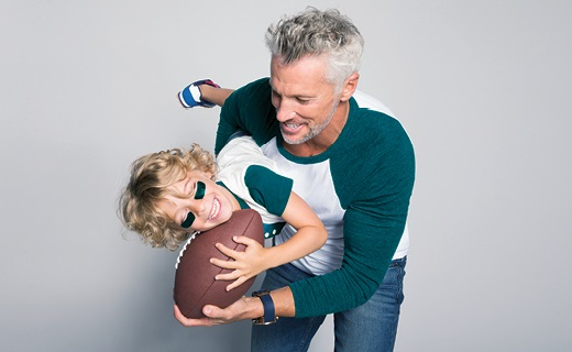 Man holding a little boy both and a football