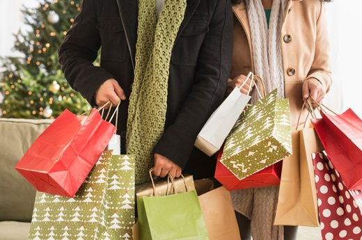Shopper wearing winter coats holding shopping bags