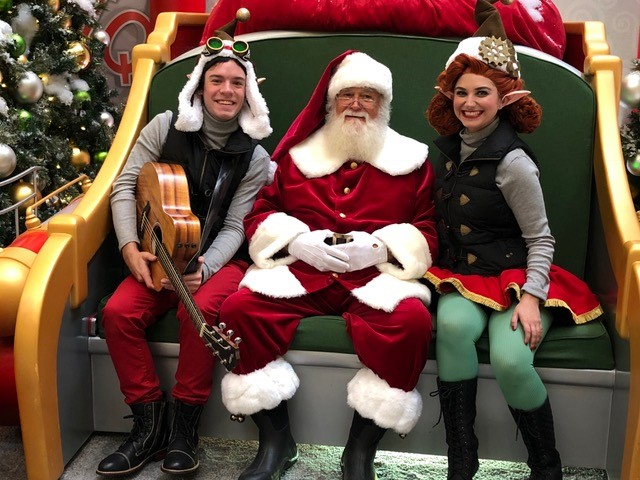 two elves sitting with Santa on his big rocket chair
