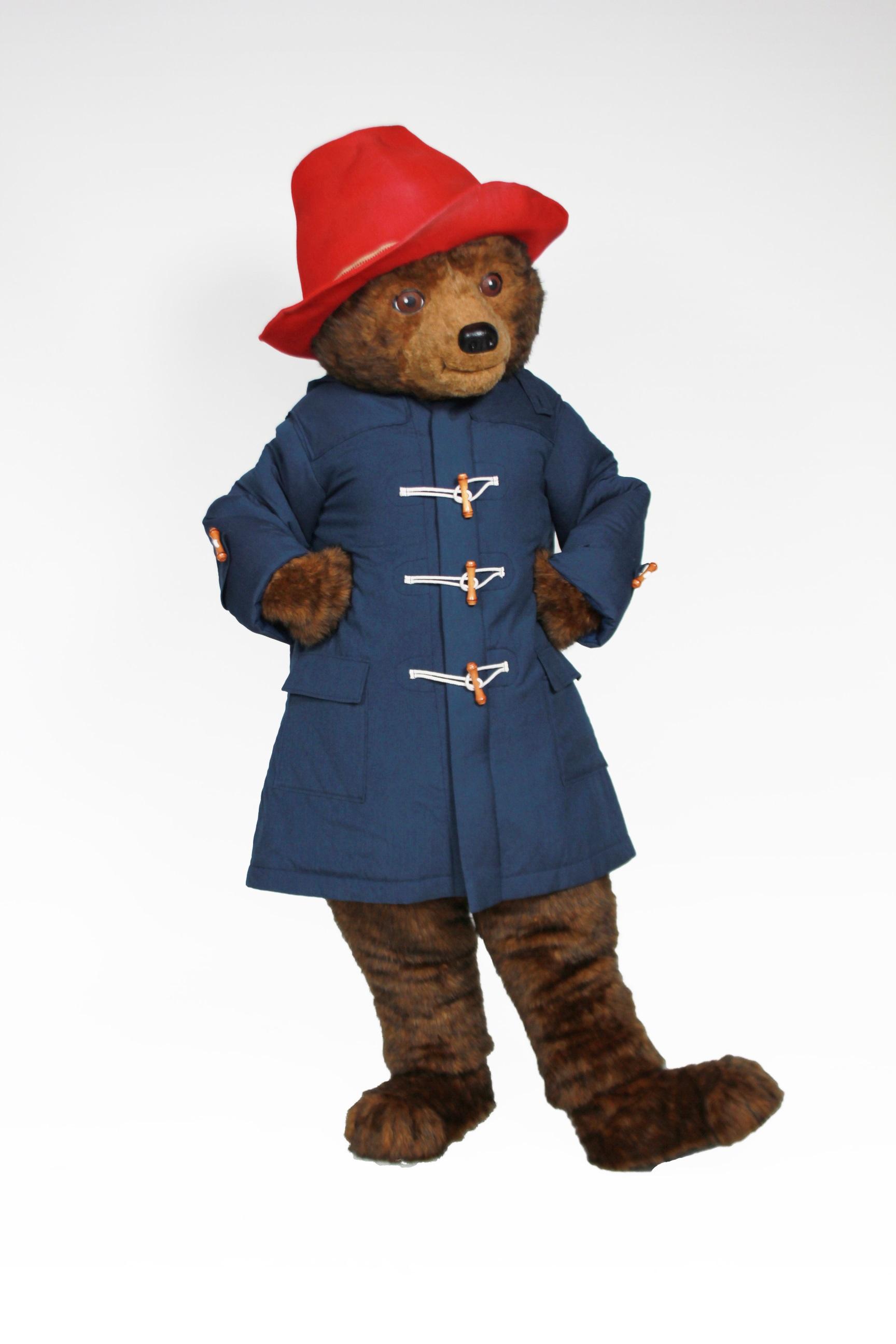 Paddington Bear wearing a blue coat and a red rain hat