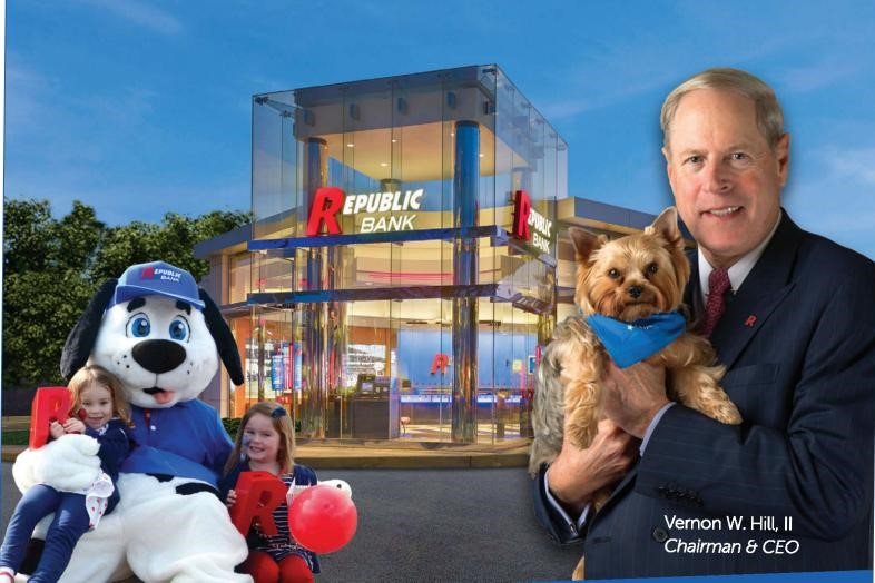 Republic bank building with dog mascot and two small children and Chairman & CEP Vernon W. Hill, II holding a small puppy