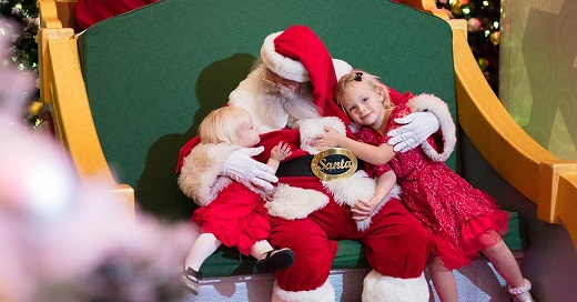 Two young girls hugging Santa in his big rocket chair