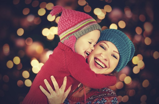 Mom and child wearing wool hats and smiling