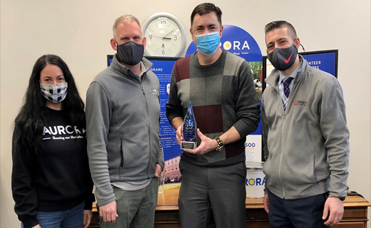 Marketing Manager Sean Ferguson gives the Nonprofit of the Month award to three members of Aurora.